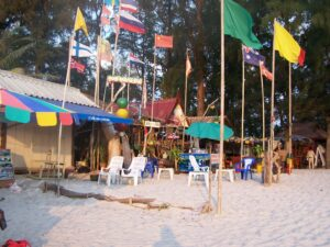 Flags of many countries in front of food and drink stands on a beach